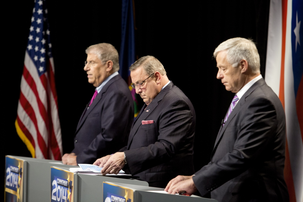 The three candidates for governor, from left independent Eliot Cutler, Republican Gov. Paul LePage and Democratic U.S. Rep. Mike Michaud, look over their notes as they prepare for Tuesday night's debate at WMTW-TV's studio in Auburn