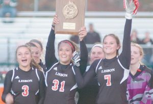LISBON HIGH SCHOOL field hockey players Courtney Lawrence (3), Arianna Kahler (31) and Molly Nicholson (7) hold up the championship plaque after a 2-1 double overtime win over Oak Hill in the Western Maine Class C title game on Thursday at Scarborough. The Greyhounds take on Winslow in the state Class C Championship on Saturday at Thomas College in Waterville. See game story on B1.