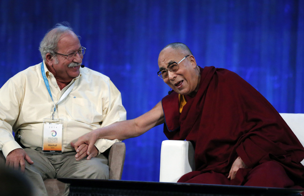 The Dalai Lama, Tibet's spiritual leader, laughs with Harvard's Kennedy School professor Marshall Ganz at the Massachusetts Institute of Technology in Cambridge on Friday.