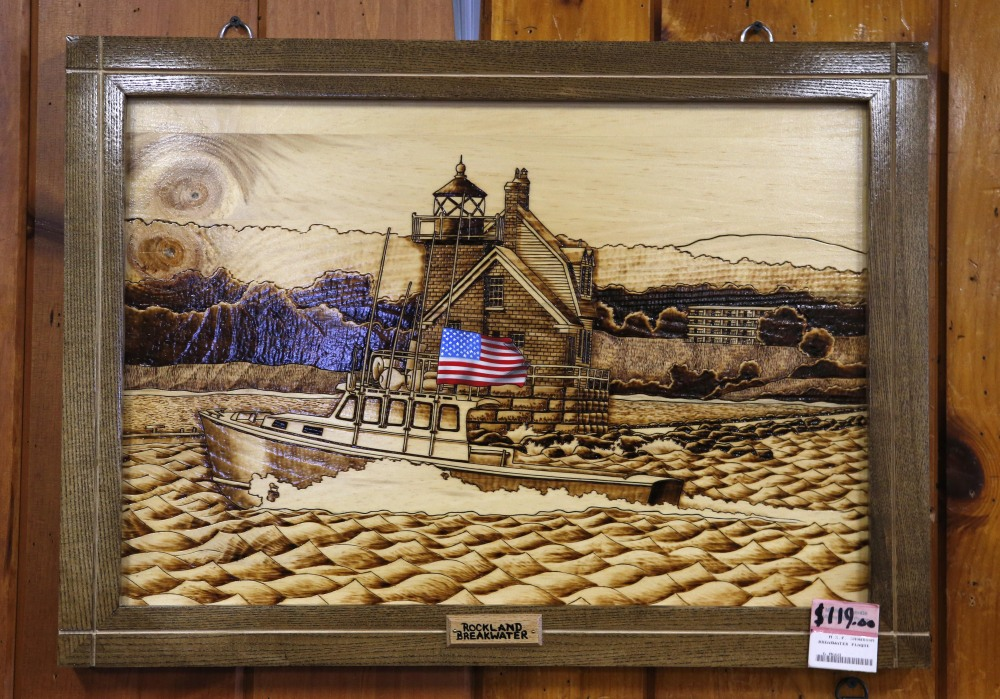A wood-burned etching depicting the nearby Rockland Breakwater lighthouse is displayed for sale at the Maine Prison Store on Friday in Thomaston. The Maine prison system has two stores that sell the handicrafts of inmates – everything from bookshelves to a model of the USS Constitution.