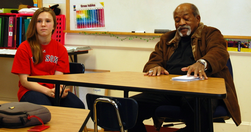 Karissa Kenyon, an eighth-grader at Wells Junior High School sits at the front of the class with former Red Sox pitcher Luis Tiant , a native Cuban who spoke with students as part of a class project on immigration. Kenyon did a project detailing immigration's effect on Major League Baseball.