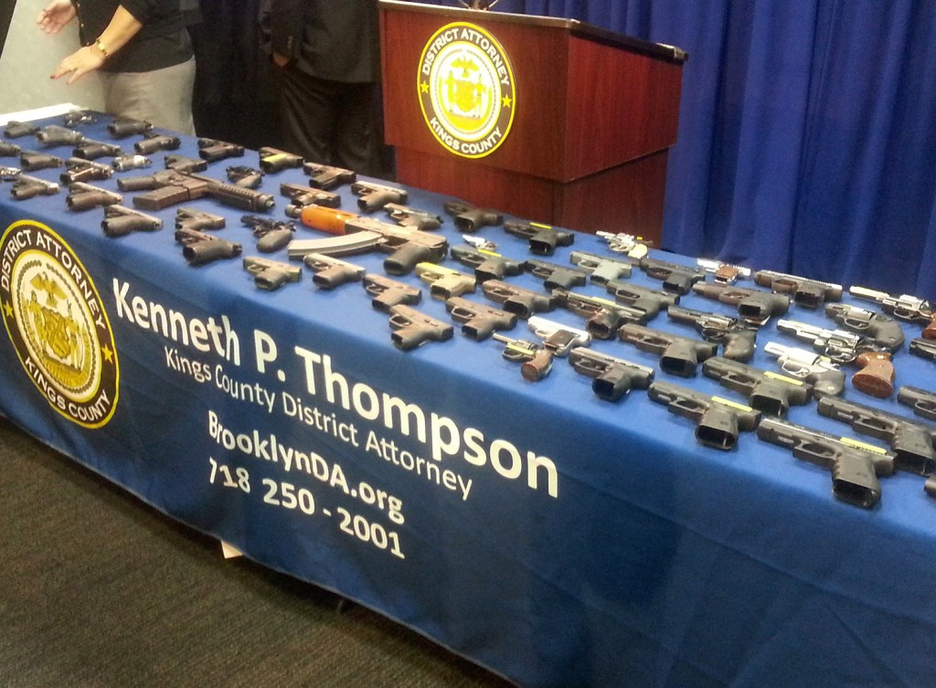 In this photo provided by the Brooklyn District Attorney's Office, a collection of handguns and two assault rifles fill a table during a news conference Tuesday. Investigators in New York arrested former Delta Airlines employee Mark Quentin Henry on Dec. 10 and charged him with transporting 153 guns on 17 commercial flights flights between Atlanta and New York.