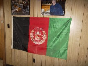 """Photo from U.S. District CourtA former Bath Iron Works employee is suing the company claiming he was subjected to harassment and discrimination because he is Muslim and Palestinian. According to documents submitted in U.S. District Court, this Afghanistan flag, given to BIW by the U.S. Marine Corps for the company's support of the United Way and Toys for Tots, continues to hang """"in plain view"""" in the main walkway at BIW despite being """"decimated with hate graffiti"""