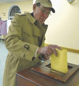 DAVID CRUMP submits his ballot at the polls at the West Bath Fire Department on Tuesday.
