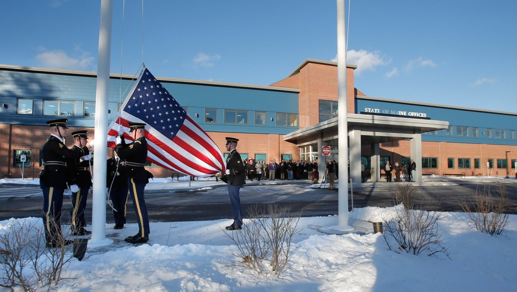 A military honor guard raises a flag Monday outside the new offices of the Department of Health and Human Services and Department of Labor in South Portland . The new building also houses regional offices of the Department of Veterans' Affairs.