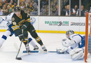 BOSTON BRUINS LEFT WING David Pastrnak (88) shoots in front of Tampa Bay Lightning defenseman Matt Carle (25) and scores against goalie Ben Bishop during the second period of an NHL hockey game in Boston on Tuesday.