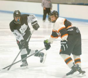 ANDREW ENO (3) of the Brunswick Dragons turns to look at a shot just released by St. Dom's Caleb Labrie. The Dragons dropped only their second game, 8-2 against the Saints at Sidney J. Watson Arena at Bowdoin College on Tuesday.
