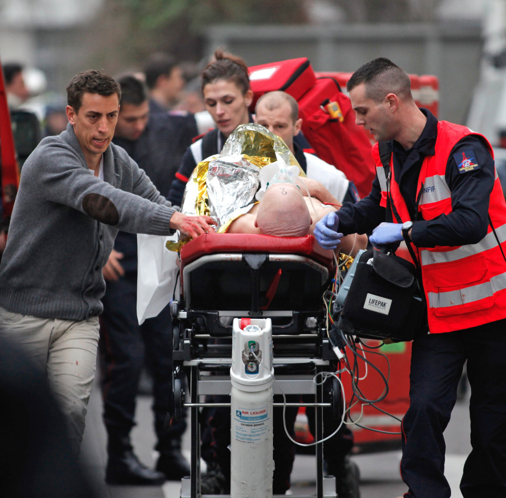 An injured person is transported to an ambulance after the shooting at the French satirical newspaper Charlie Hebdo's office, in Paris, Wednesday.