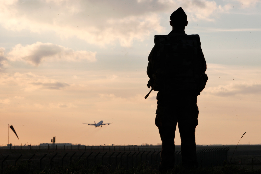 A plane takes off as a French soldier patrols at the Roissy Charles de Gaulle airport, in Roissy, north of Paris, on Saturday. France ordered 10,000 troops into the streets Monday to protect sensitive sites – nearly half of them to guard Jewish schools – as it hunted for accomplices to the Islamic militants who left 17 people dead as they terrorized the nation.