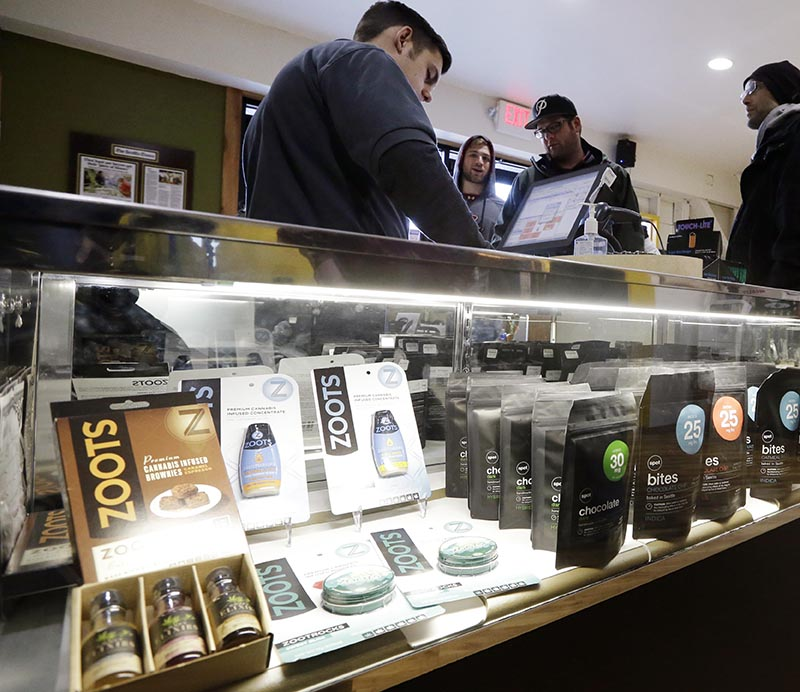 Cannabis City clerk John Golby, left, helps customers looking over a display of marijuana products at the shop in Seattle.