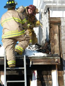 Firefighters work from atop the shop, attached to the house, to find a lingering hot spot detected with a thermal imaging camera.
