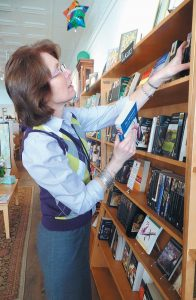JULIE SHEA, co-owner of The Mustard Seed Bookstore, rearranges books on the classics shelf of her Bath store.