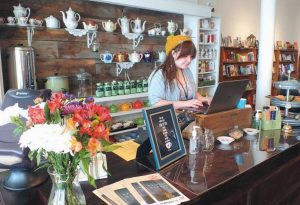 OLIVIA SHIPSEY, a junior at Morse High School, works the register at The Mustard Seed Bookstore in Bath.
