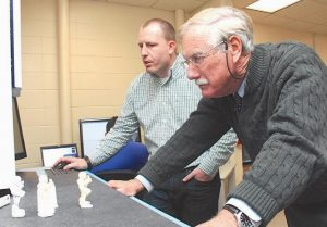 SEN. ANGUS KING, right, examines a 3D scanner Friday during a tour of RollEase at Brunswick Landing with Tom Brown, a design engineer.
