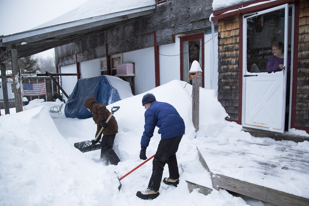 Boy Scouts clear snow from around Nancy Taylor's house in Freeport. Taylor feared that she couldn't get out of the home if she had a second heart attack.