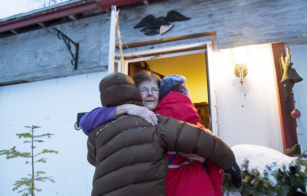 Boy Scout patrol leaders Harrison Holmes, 12, left, and Sam Yankee, 11, get a hug from Nancy Taylor after a dozen Scouts cleared 4 feet of snow from around her house. Taylor was worried that she couldn't get out of the home if she had a second heart attack.