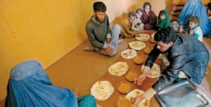 AN AFGHAN REFUGEE FAMILY who arrived to Afghanistan through Pakistan's border crossing prepare to eat at the International Organization for Migration center, in Torkham, east of Kabul, Afghanistan, in this March 11 photo.
