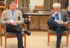 SEN. CHRIS JOHNSON and Rep. Mick Devin review Gov. Paul LePage's twoyear budget proposal at a public forum on Monday night.