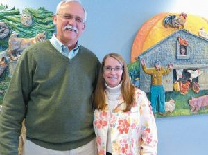 BOWDOIN CENTRAL SCHOOL'S George Jenkins is pictured with school secretary Karen Mayo, who as he approaches retirement, said he couldn't have done his job without. They are shown near artwork that hangs near the entrance of the school.