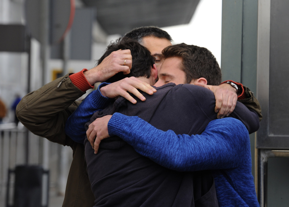 People comfort each other as they arrive at the Barcelona airport in Spain on Tuesday.