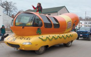 THE OSCAR MAYER Weinermobile was all decked out for St. Patrick's Day as it rolled into Bath for the annual Blarney Days parade on Saturday. At left, the Maine Public Safety Pipe and Drum Corps also took part.