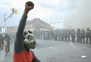 A DEMONSTRATOR raises his fist as police stand in formation as a store burns Monday following the funeral of Freddie Gray in Baltimore.