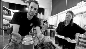 KOBY HARRIS, brewery production manager, left, and Sandra Cain, assistant director of retail operations, present their freshly brewed beers at Innovation Brew Works in the California State Polytechnic University, Pomona in Pomona, Calif., in this March 19 file photo.