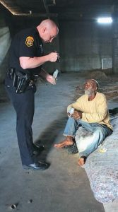 CLEARWATER POLICE Officer Eric Mitchell, left, questions Jonathan Russell, who has been living under an abandoned former office tower in Clearwater, Fla. Russell told Mitchell he has been homeless since being released from jail last year.