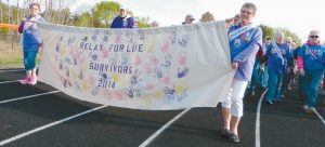 AT RIGHT, Donna Cox, left, and Cynthia Wooley carry last year's Relay For Life survivor banner around the track at Brunswick High School Friday during the all-night fundraiser for the American Cancer Society. During a regular self breast exam Wooley noticed something was wrong and was diagnosed with breast cancer, which had spread to the lymph nodes. Fortunately it was caught early and she received her last treatment at the end of January.