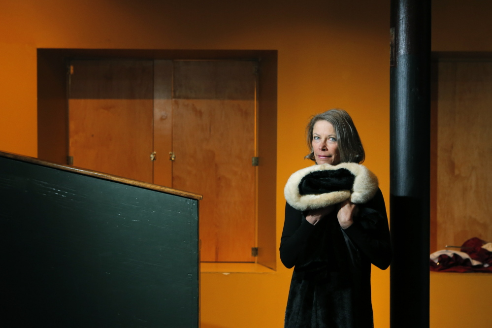 """Elizabeth Peavey with a coat that belonged to her mother, which she uses as a prop in """"My Mother's Clothes Are Not My Mother."""" Peavey has retooled the one-woman play and recently performed it in New York. She brings it back to Maine for two shows in June."""