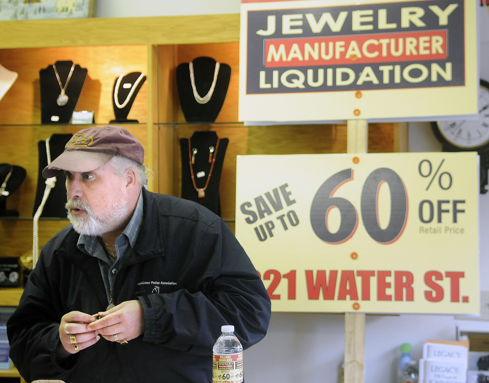Above, a sign for a discount sale at The Village Jeweler store sits on the street in front of the business in Gardiner. State officials have told owner Daniel Lane to stop using sign walkers to advertise a liquidation sale. Below, Lane appraises a ring in front of a sign that officials told him to stop using off-premises.