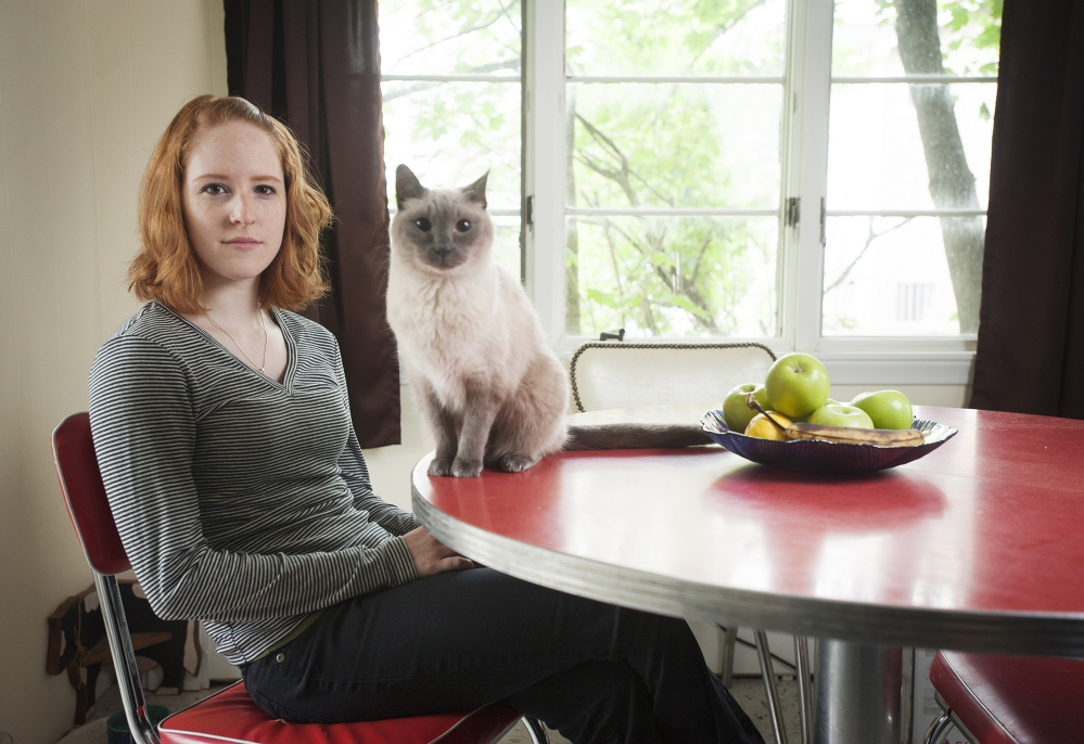 Sarah Fearing, who graduated from the University of Maine in May, says she and her parents prepared for the financial burden of school, but she still wound up with some debt. Sitting with her cat Sam at her home in Brewer, Fearing said her dad deposits bottle-return funds into her bank account to help defray costs.