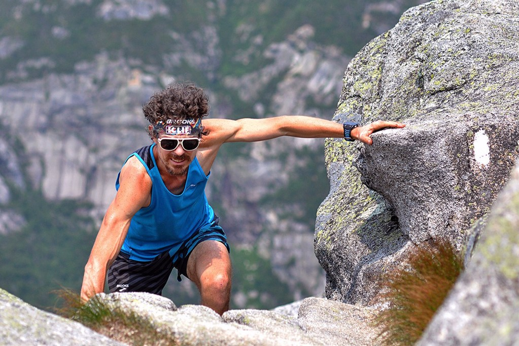 Scott Jurek climbs to the summit of Mount Katahdin on Sunday before completing the Appalachian Trail in what he claims is record time. Luis Escobar/Brooks Running Company via AP