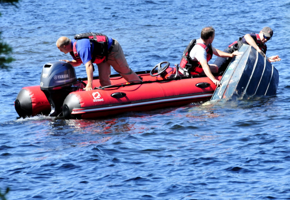 Skowhegan firefighters including Chief Shawn Howard, left, secure a sunken boat after it and fisherman Llewellyn Ryder, 66, of Clinton overturned in the choppy Lake George in Canaan on Wednesday. Ryder got out and made it to shore wet but unharmed.