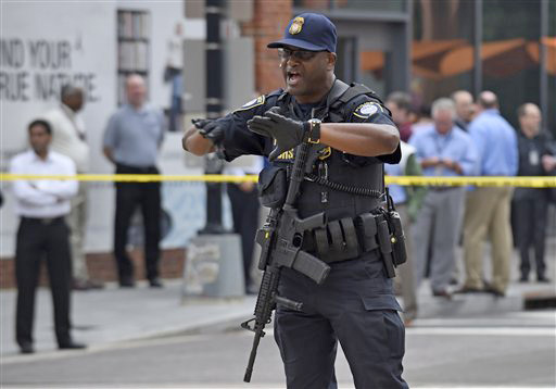 Police near the Washington Navy Yard in Washington tell members of the media to move. A lockdown was underway Thursday morning across the Washington Navy Yard campus after reports of shots fired. The Associated Press