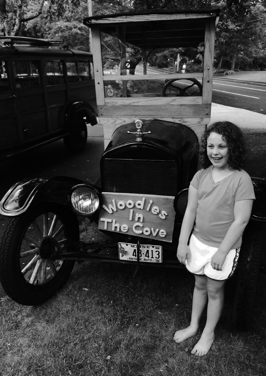 """Nineyear old Lilly Grace of York made the sign that is shown with her father's Model T Ford Woody, which will be at the """"Woodies in the Cove"""" show."""