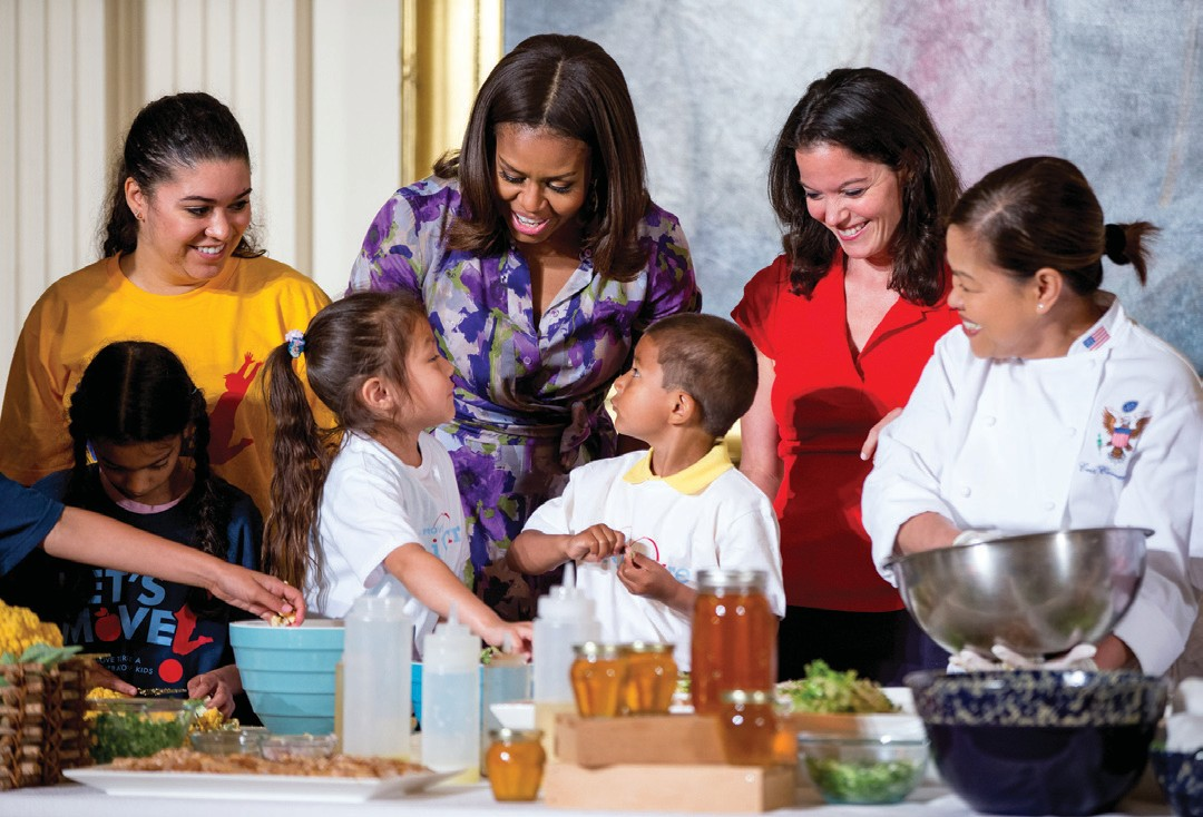 First lady Michelle Obama, accompanied by Lets Move! Executive Director Deb Eschmeyer, second from right, talks with Oneida Gonzalez, 5, center left, and Jefferson Lopez- Martinez, 5, center right, of CentroNia Daycare Center in Washington, D.C. as they help prepare food harvested from the White House Kitchen Garden on June 3 in the East Room at the White House in Washington.