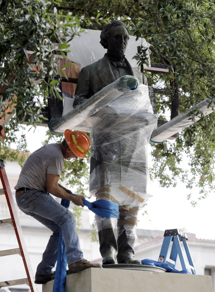Workers wrap protective materials around a statue of Confederate President Jefferson Davis as they prepare to move the sculpture on the University of Texas campus Sunday. The Davis statue, which has been targeted by vandals and had come under increasing criticism, will be placed in the school's Dolph Briscoe Center for American History as part of an educational display.
