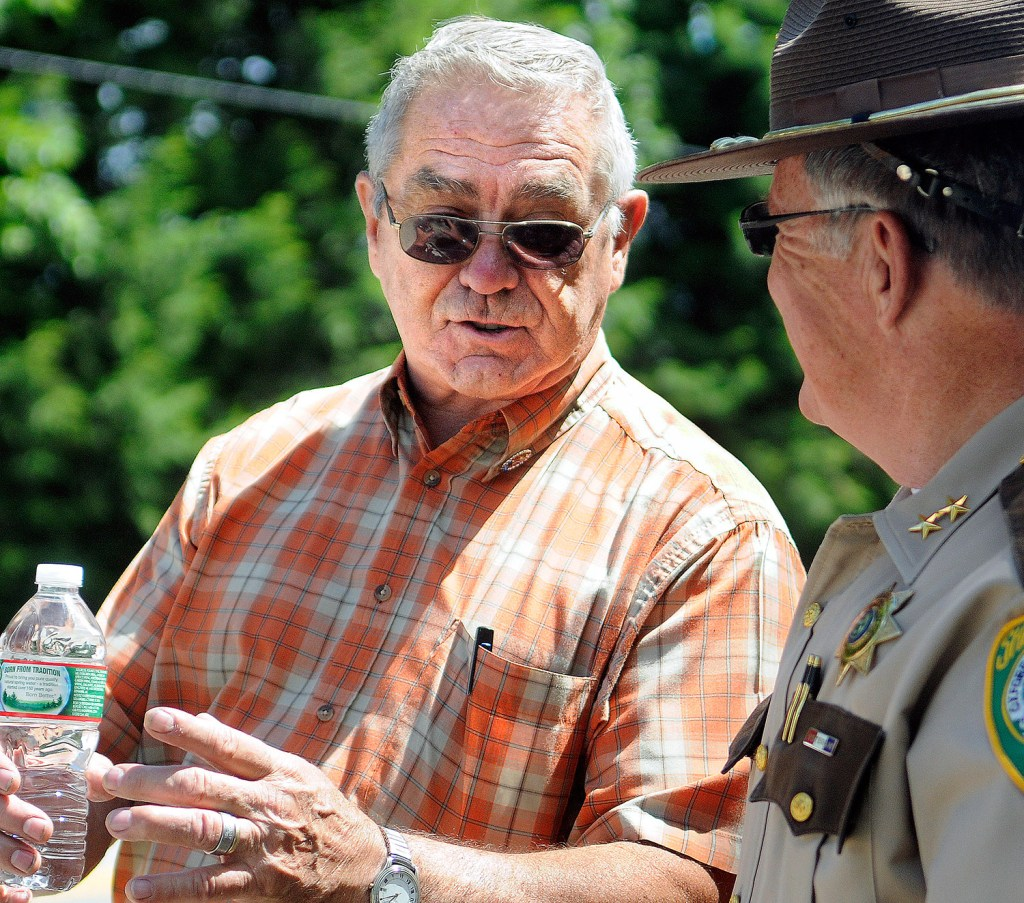 Kim Moreau's father, Dick, speaks with Oxford County Sheriff Wayne Gallant on Thursday across from a home on Route 108 in Canton where police searched for her remains. Andy Molloy/Kennebec Journal
