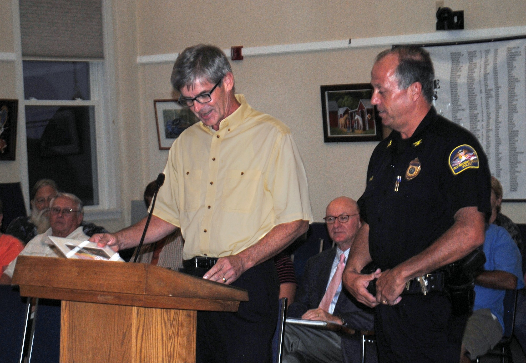 Town Manager Larry Mead honors Deputy Police Chief Keith Babin, who is retiring later this month, Tuesday night at the Town Council chambers.