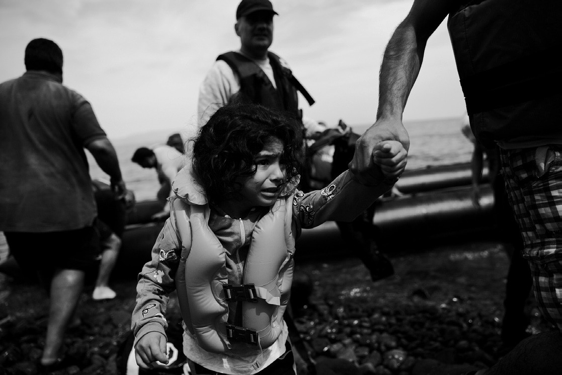 A young migrant girl is helped ashore as she arrives with others aboard a dinghy after crossing from Turkey to Lesbos island, Greece on Wednesday.