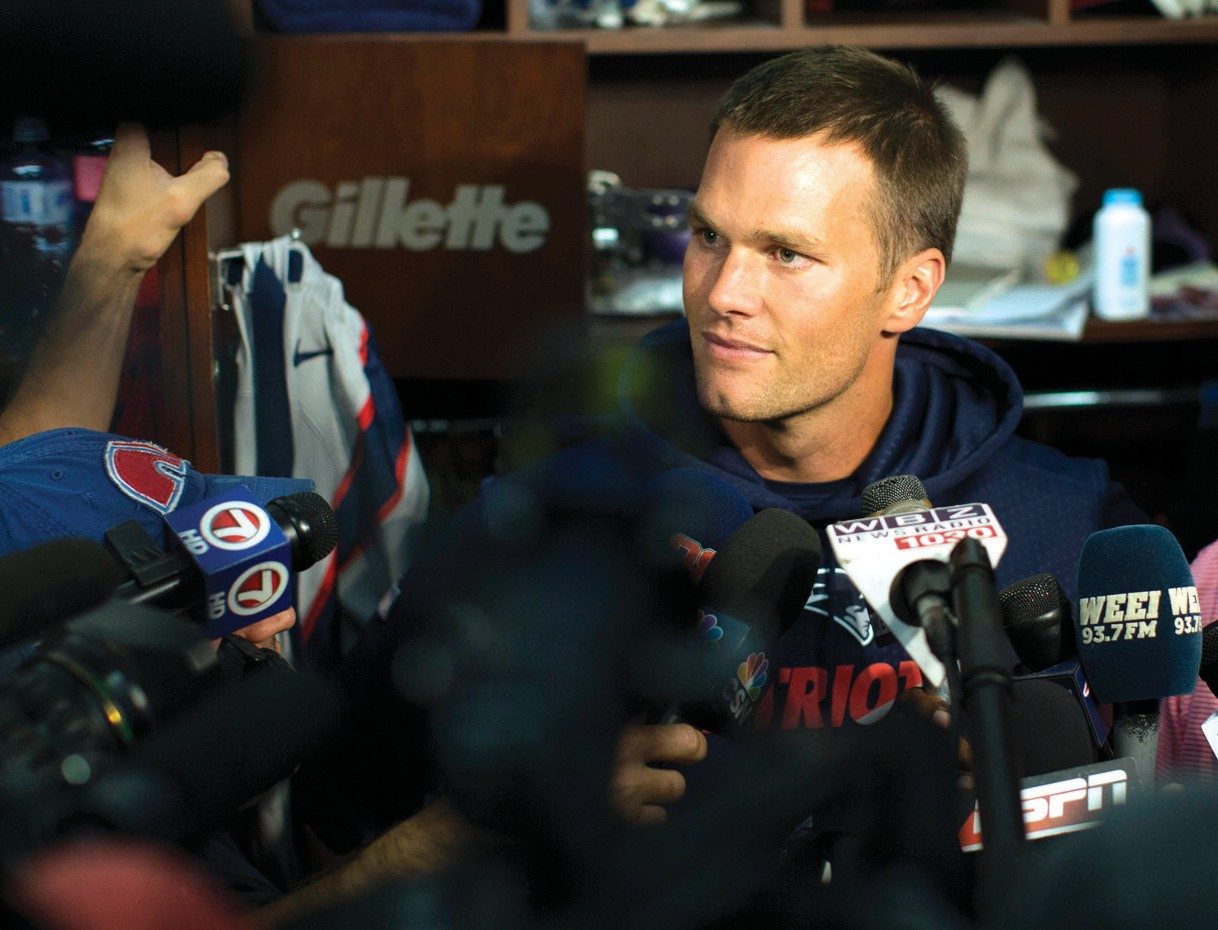 New England Patriots quarterback Tom Brady speaks to members of the media in the locker rook at Gillette Stadium prior to the team's practice in Foxborough, Mass, Sunday.