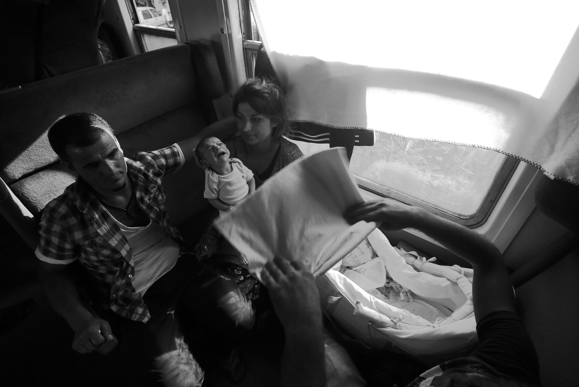 Amina Asmani, right, with her baby and husband travel on a train taking them towards Serbia, near the southern Macedonian town of Demir Kapija on Aug. 19.