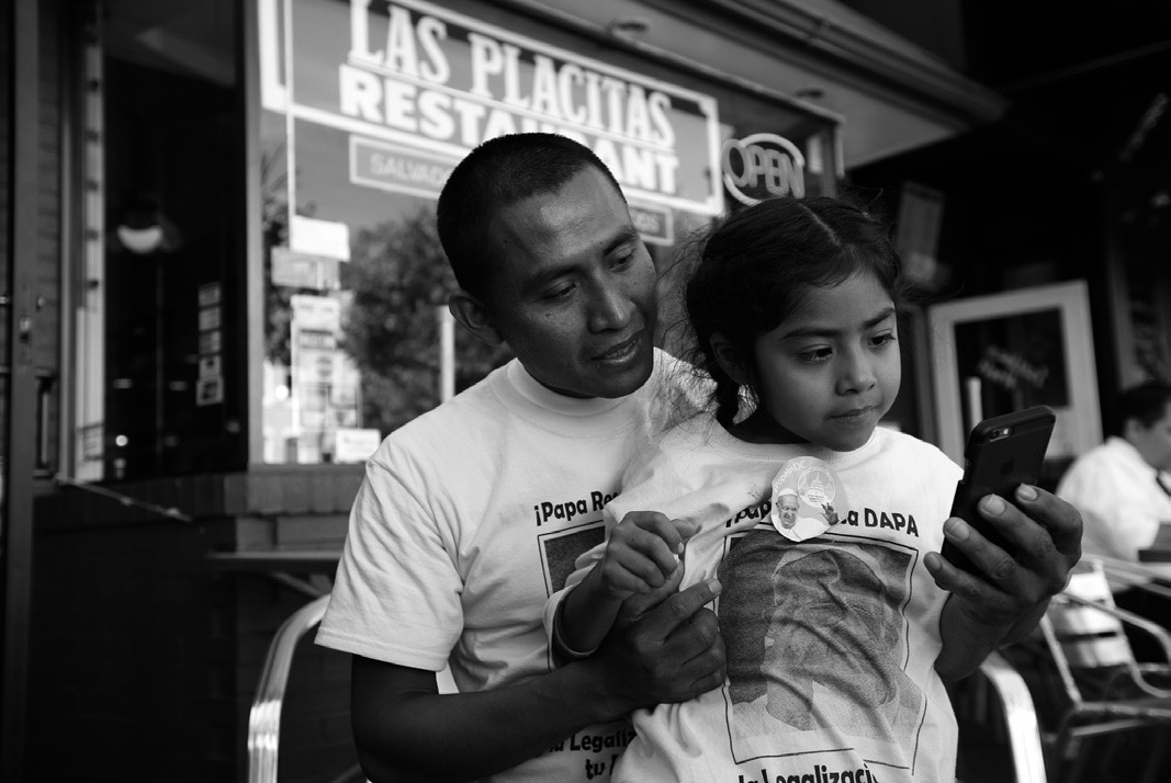 Raul Cruz, from suburban Los Angeles, holds his daughter Sophie Cruz, 5, as they talk to Sophie's mother via telephone, Wednesday in Washington. Sophie crossed a police barricade to greet Pope Francis during his parade.