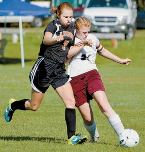 LISBON HIGH SCHOOL'S Emma Houle, left, and Monmouth Academy's Cheyenne Gray battle for the ball during their game in Monmouth on Saturday.
