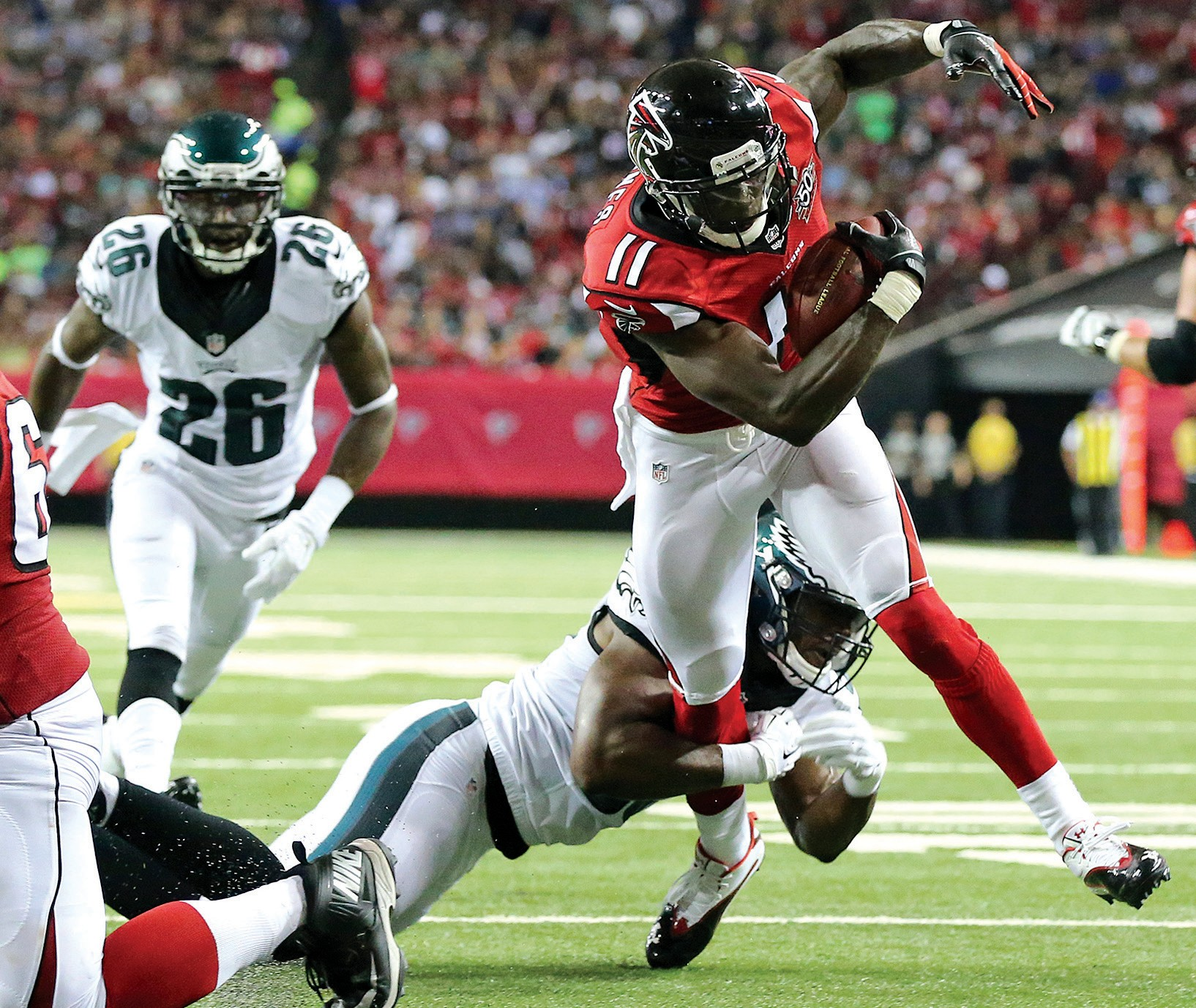 Falcons wide receiver Julio Jones catches a pass and breaks a tackle attempt by Eagles linebacker DeMeco Ryans on his way to the endzone for a touchdown during an NFL football game on Monday in Atlanta.