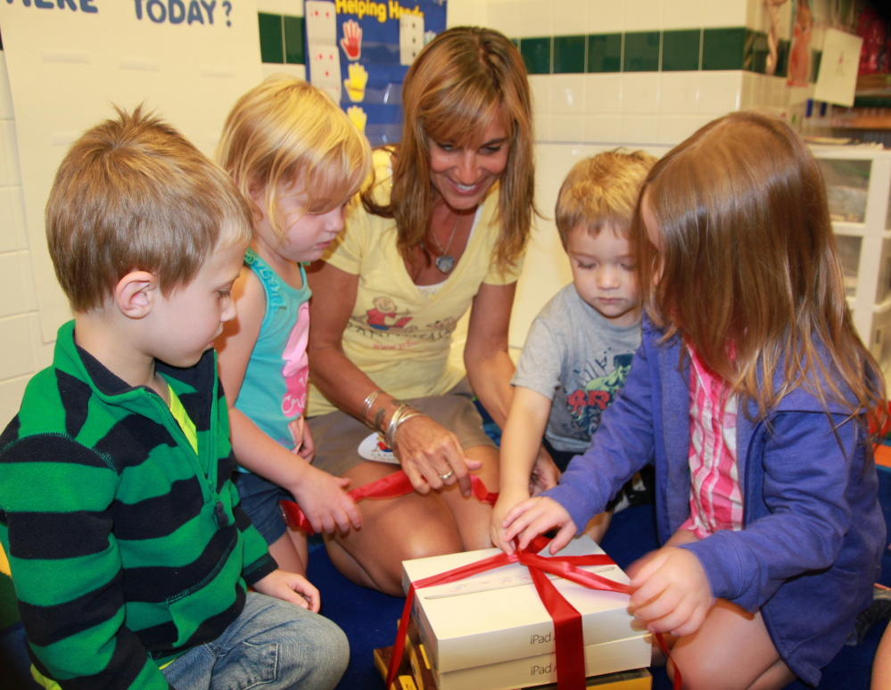 Children at the Fraser-Ford Child Development Center's daycare help Leslie Morissette unwrap two new iPads and cases donated to the center by Grahamtastic Connection.