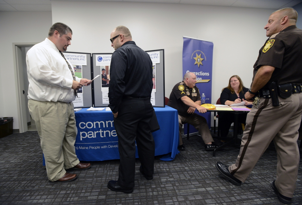 Steven Cay, left, a recruiter with Community Partners Inc., speaks with Matthew Ferrante, center, of South Portland during Wednesday's job fair at the Greater Portland CareerCenter.
