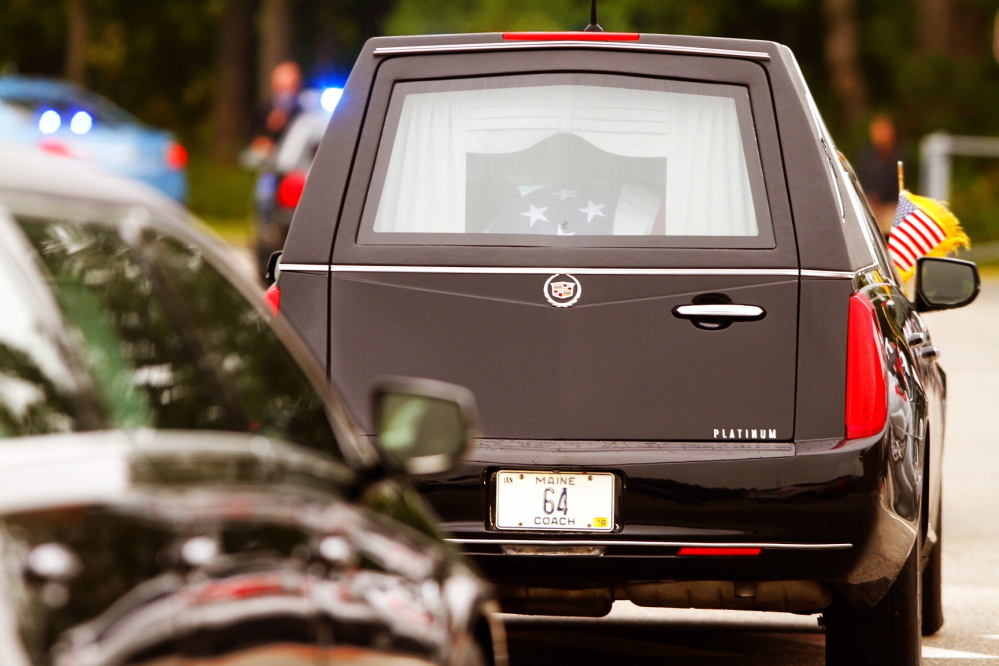 The hearse carrying Leon Gorman's flag-draped casket from the Westbrook Performing Arts Center after his memorial service Sunday.