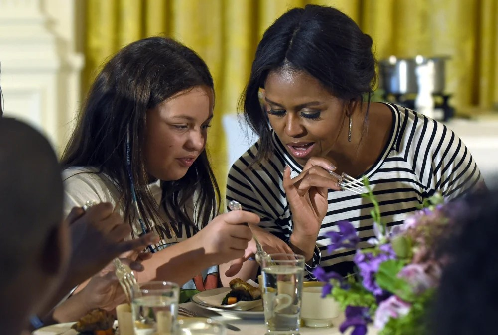 Michelle Obama and a student look over their plates as they dine in the East Room of the White House last fall, when school lunch rules pitted Republicans seeking full exemptions for some schools against the first lady ensuring kids get good nutrition.